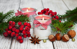 Christmas decorations candles in glass jars with fir. On a old wooden table Royalty Free Stock Image