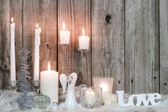 Christmas decorations and candles by wood background Royalty Free Stock Photo