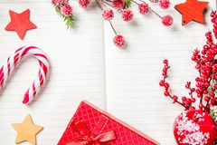 Christmas decorations, candy cane, frozen red berries, stars and gift box frame on notebook, copy space for text. Can be used for. Christmas or new year project royalty free stock photography