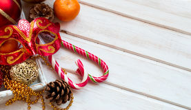 Christmas decorations, candy sticks, mask, bumps on the wooden t Royalty Free Stock Photography