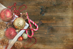 Christmas decorations, candy sticks, mask, bumps on the wooden t. Mask, red and gold Christmas balls, beads, cones, Christmas decorations Stock Photo