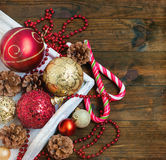 Christmas decorations, candy sticks, mask, bumps on the wooden t. Mask, red and gold Christmas balls, beads, cones, Christmas decorations Stock Photography