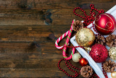 Christmas decorations, candy sticks, mask, bumps on the wooden t. Mask, red and gold Christmas balls, beads, cones, Christmas decorations Stock Photos