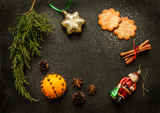 Christmas decorations on chalkboard - background layout. Vintage christmas decorations, ginger cookies and spices on black chalkboard from above - background Stock Photos