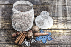 Christmas decorations, cinnamon, jar with frost and nuts, walnuts, hazelnuts.Toned image.Snow drawn. Royalty Free Stock Photo