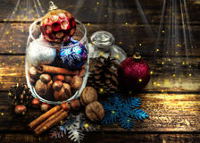 Christmas decorations, cinnamon, jar with nuts.Walnuts, hazelnuts.Toned image with the effect of shooting at midnight. Stock Image