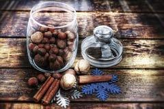Christmas decorations, cinnamon, jar with nuts.Walnuts, hazelnuts.Toned image. Royalty Free Stock Image
