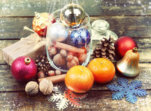 Christmas decorations, cinnamon, jar with nuts.Walnuts, hazelnuts.Toned image. Selective field of focus. Royalty Free Stock Image