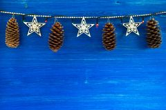 Christmas decorations with cones and Christmas lights on the blue wooden background. Stock Image