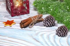 Christmas Decorations with cup of hot cocoa, lamp with candle, cinnamon sticks, pine, fir branch on wooden light blue table. Flat Royalty Free Stock Photo