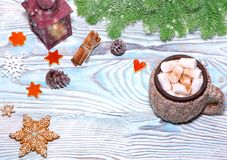 Christmas Decorations with cup of hot cocoa, lamp with candle, cinnamon sticks, pine, fir branch on wooden light blue table. Flat Stock Images