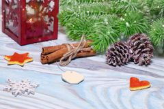 Christmas Decorations with cup of hot cocoa, lamp with candle, cinnamon sticks, pine, fir branch on wooden light blue table. Flat Stock Photography