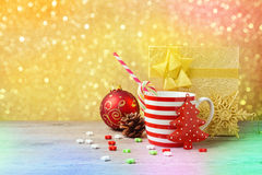 Christmas decorations and cup on wooden table over gold bokeh background Stock Photo