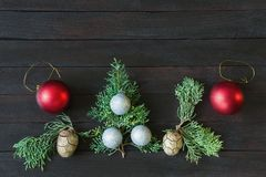 Christmas decorations on dark background. Flat lay, free space. Christmas decorations on dark background. Colorful Christmas balls, cypress foliage and cones stock image