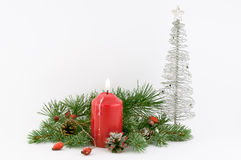 Christmas Decorations. Christmas decoration with red candle, branches of a Christmas tree and decorative silver tree on a white background royalty free stock images