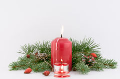 Christmas Decorations. Christmas decoration with red candles, branches of Christmas tree hips   on a white background royalty free stock images