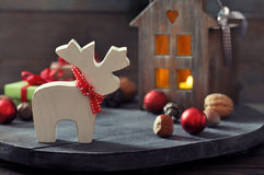 Christmas decorations. Christmas decoration in shape of elk with lantern on wooden background Stock Image