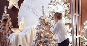 Christmas decorations, family time, child next to the Christmas tree. Kid playing at home. Xmas winter holiday concept. Happy New Year and happy holidays stock video