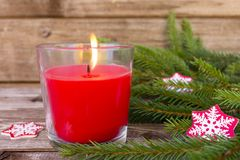 Christmas decorations, fir branches and red flaming candle on vintage wooden board background royalty free stock photography