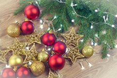 Christmas decorations with fir branches on wooden background, balls and stars, gold and red royalty free stock photography