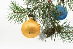 Christmas decorations and fir cones on the white background. Christmas decorations balls and fir cones hanging from the Christmas tree on the white background stock images