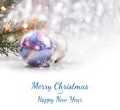 Christmas decorations with fir tree branch on wooden background with snow, blurred, sparking, glowing and text Merry Christmas Royalty Free Stock Photo