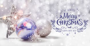 Christmas decorations with fir tree branch on wooden background with snow, blurred, sparking, glowing and text Merry Christmas Stock Photography