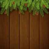 Christmas decorations with fir tree branches and pine cones on brown wooden background. Christmas background and spruce branches with pine cones. Holiday Stock Images