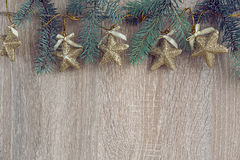 Christmas decorations with a fir-tree hanging over wooden backgr Royalty Free Stock Images