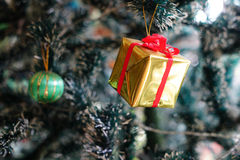 Christmas decorations focusing on gift box hanging on pine tree Stock Images