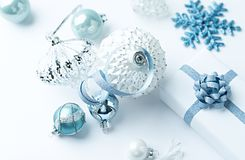 Christmas decorations and a gift box on white background. Close-up. Copy space stock image
