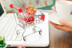 Christmas decorations and gift boxes in shopping cart on laptop, Online shopping Royalty Free Stock Photo