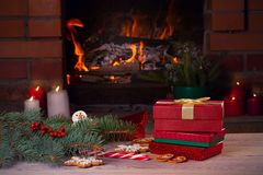 Free Christmas Decorations, Gifts And Cookies On Wooden Table Beside Cosy Open Fire Place Royalty Free Stock Images - 130907949