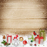 Christmas decorations and gifts in the snow on a wooden background Stock Photos