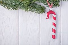 Christmas decorations glass candy cane and christmas tree branch on a white background. Free space. Christmas decorations glass candy cane and christmas tree royalty free stock image