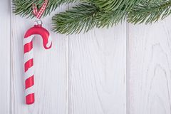 Christmas decorations glass candy cane and christmas tree branch on a white background. Free space. Happy New Year. Christmas decorations glass candy cane and stock photos