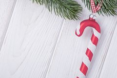 Christmas decorations glass candy cane and christmas tree branch on a white background. Free space. Happy New year. Christmas decorations glass candy cane and royalty free stock image