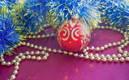 Christmas decorations, golden beads, blue tinsel and red ball with gold pattern, lie on a red background. Royalty Free Stock Image