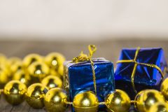 Christmas decorations, golden and blue. Christmas decoration with golden pearls and blue packets on a wooden base Stock Photos