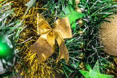 Christmas decorations. Golden Christmas bow on a background of green tinsel. Stock Photos