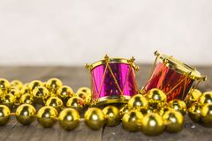 Christmas decorations, golden and colorful. Christmas decoration with golden beads and colorful drums on a wooden surface Royalty Free Stock Photos