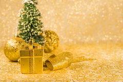 Christmas decorations. Golden Christmas ornaments, golden Christmas decoration in present box shaped, golden shiny ribbon and snowed Christmas tree on golden Stock Image