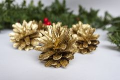 Christmas decorations and golden pine cones. Multiple Golden pine cones and Christmas Decorations stock image
