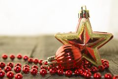 Christmas decorations, golden and red. Christmas decoration with red pearls and red glossy ball and star on a wooden surface Stock Photography