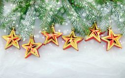 Christmas decorations, green and golden. Christmas decoration with green Christmas twigs and shiny stars on a white background Stock Photos