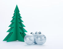 Christmas decorations and green paper tree. Christmas decorations and green paper tree on a white background Royalty Free Stock Photo