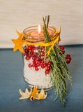 Christmas hand made candle with red berries craft on the blue tablecloth Royalty Free Stock Photography