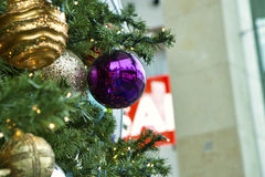 Christmas Decorations. Hanging in front of a partially hidden Sale sign during the most lucrative season of the year for retail sales Royalty Free Stock Photo