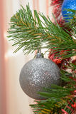 Christmas decorations hanging on a pine tree with glitter, Stock Photo