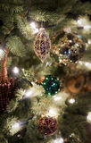 Christmas decorations hanging on a tree. Ornamented red and golden balls and decorations hanging on illuminated christmas tree with more fancy decorations on Royalty Free Stock Photography